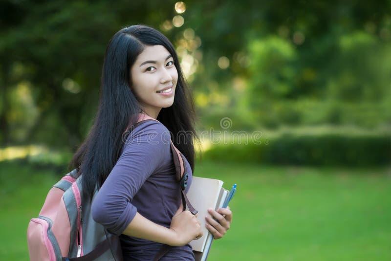 Asiatisk kvinnahögskolestudent på universitetsområde royaltyfria foton
