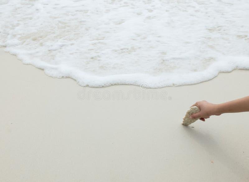 Asiatisk kvinnahand som rymmer stenen för vitt hav på hörnet på rengöringen och den tomma vita sandstranden med havsvågen som ram arkivbilder