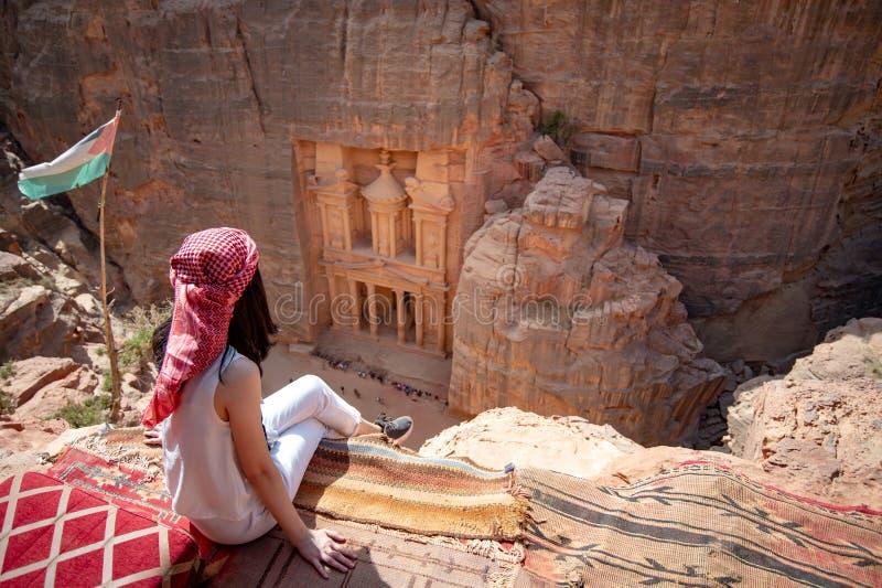 Asiatisk kvinnahandelsresande som sitter i Petra, Jordanien royaltyfri foto