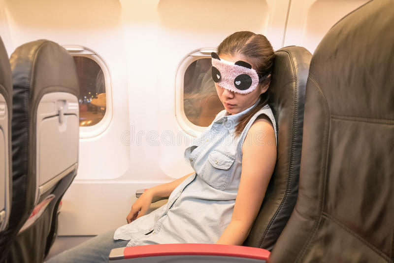 Asiatisk kvinnahandelsresande som sover i flygplanet arkivfoto