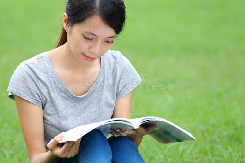 Asiatisk kvinnaläsebok royaltyfri bild