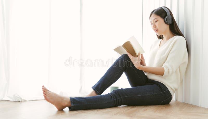 Asiatisk kvinnaläsebok för stående och koppla av med kaffe hemma royaltyfria bilder