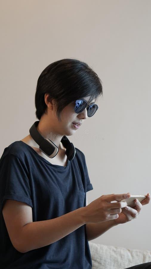 Asiatisk kvinnalivsstil genom att använda smartphonen, medan genom att använda hörlurar arkivfoto