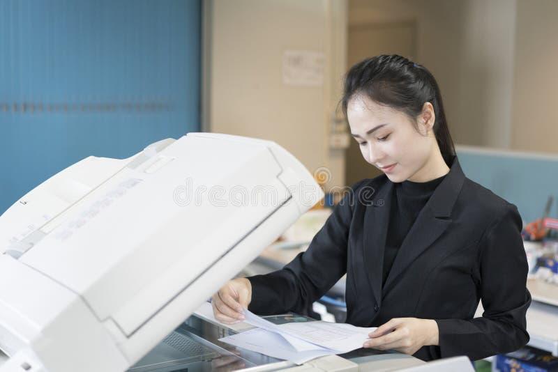 Asiatisk kvinnasekreterare som använder kopieringsmaskinen arkivfoton