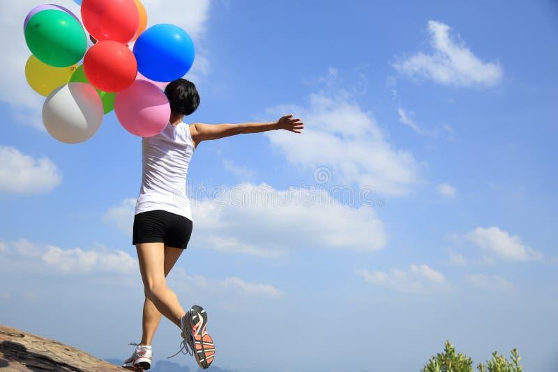 Asiatisk kvinnaspring på bergmaximum vaggar med kulöra ballonger royaltyfri foto