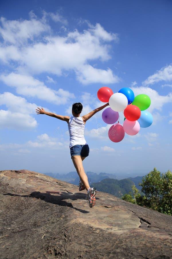 Asiatisk kvinnaspring på bergmaximum vaggar med kulöra ballonger fotografering för bildbyråer