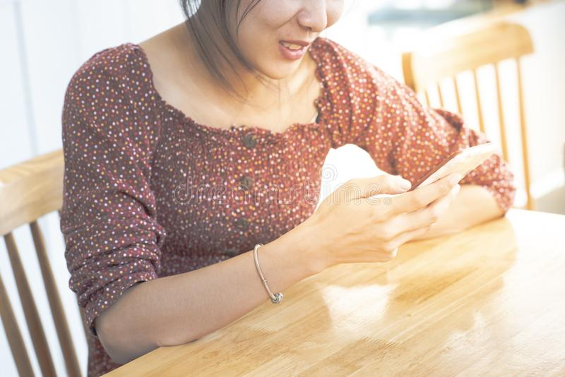 Asiatisk kvinnatonåring i tillfällig klänning med leende på den smarta mobiltelefonen för framsidahandbruk i kaffeahop, livsstilb royaltyfria bilder
