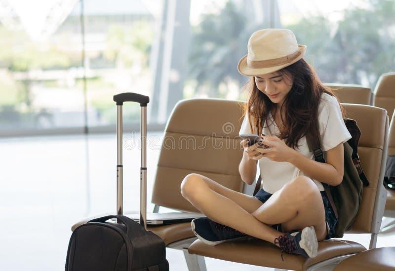 Asiatisk kvinnatonåring som använder smartphonen på sammanträde för flygplatsterminal med den bagageresväskan och ryggsäcken för  arkivfoto