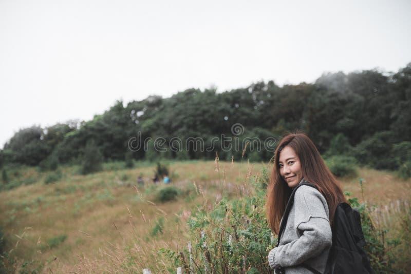 Asiatisk kvinnaturist som går och trekking längs bergen i tropisk skog med mening lyckligt arkivbild