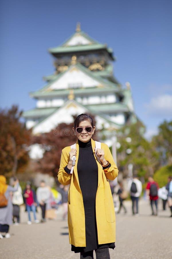 Asiatisk kvinnaturist som tar ett fotografi på osaka slott en av mest populär resande destination i Japan arkivfoto