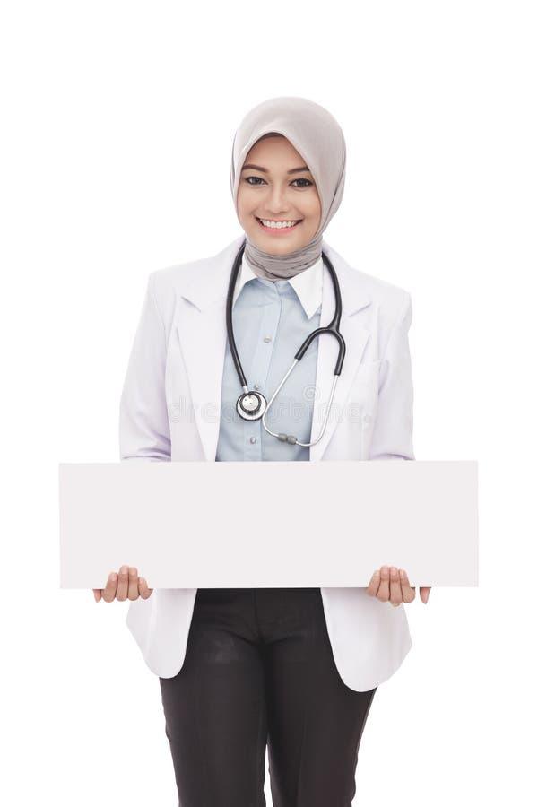 Asiatisk kvinnlig doktor med det vita brädet för stetoskopinnehavmellanrum royaltyfria foton