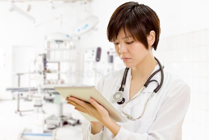 Asiatisk kvinnlig doktor som använder minnestavladatoren i klinik royaltyfria foton