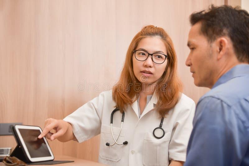 Asiatisk kvinnlig doktor som använder minnestavlan med den manliga patienten arkivbild