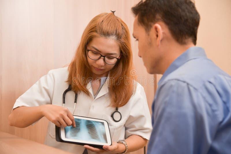 Asiatisk kvinnlig doktor som använder minnestavlan med den manliga patienten arkivfoton