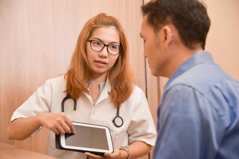 Asiatisk kvinnlig doktor som använder minnestavlan med den manliga patienten arkivfoto