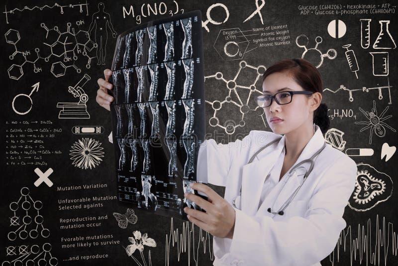 Asiatisk kvinnlig doktorshållröntgenstråle i labb arkivbild