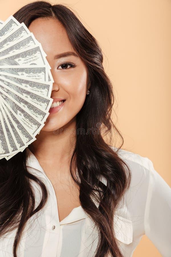 Asiatisk kvinnlig för brunett som ler och täcker halva av hennes framsida med royaltyfri foto