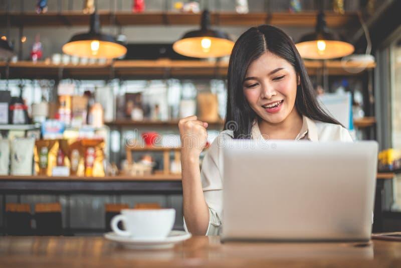 Asiatisk kvinnlig freelancer som g?r lycklig gest, genom att lyfta handen, n?r genom att anv?nda b?rbara datorn i kaf? Aff?rs- oc arkivfoton