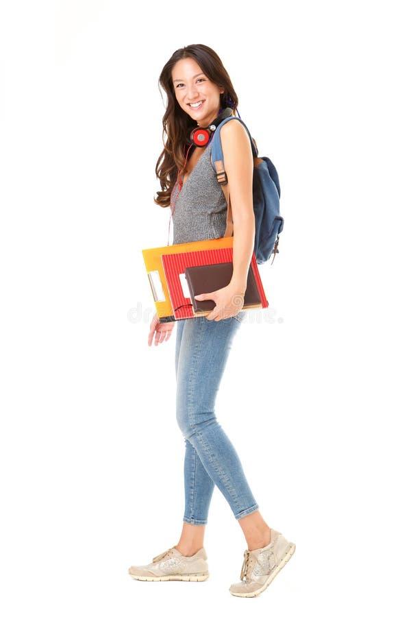 Asiatisk kvinnlig högskolestudent för full kropp som går mot isolerad vit bakgrund med böcker och påsen arkivfoto