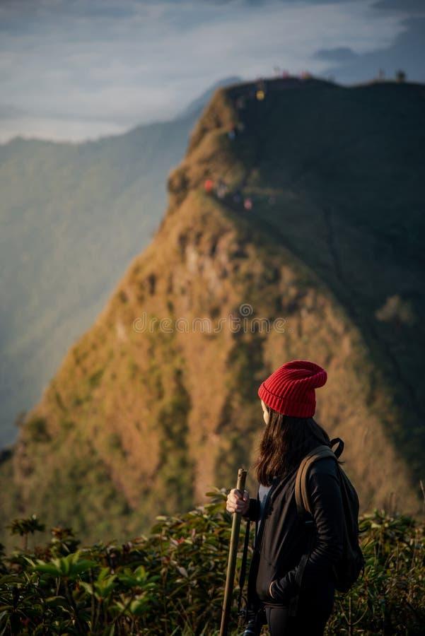 Asiatisk kvinnlig handelsresande som ser berglandskap royaltyfri foto
