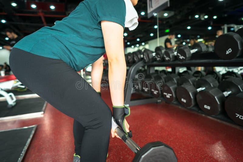 Asiatisk kvinnlig kondition som utför göra deadliftövning med viktstången royaltyfria bilder