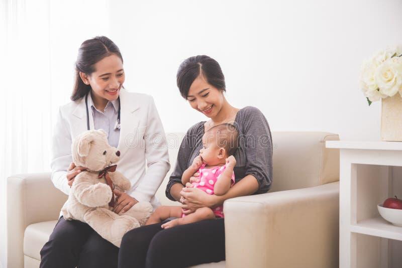 Asiatisk kvinnlig pediatrisk visning en docka till behandla som ett barnflickan i kvickhet fotografering för bildbyråer