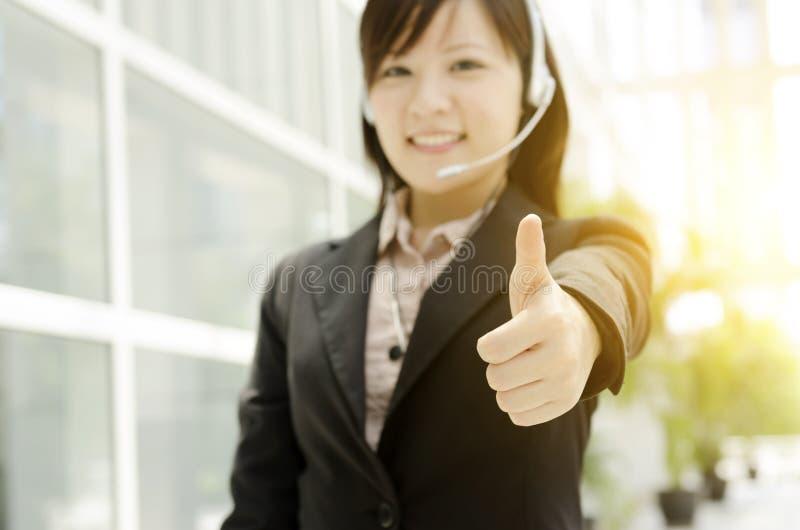 Asiatisk kvinnlig receptionisttumme upp royaltyfria bilder