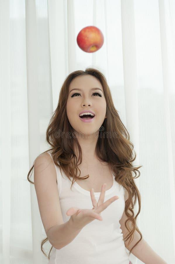 Asiatisk kvinnlig som kastar ett rött äpple royaltyfri bild