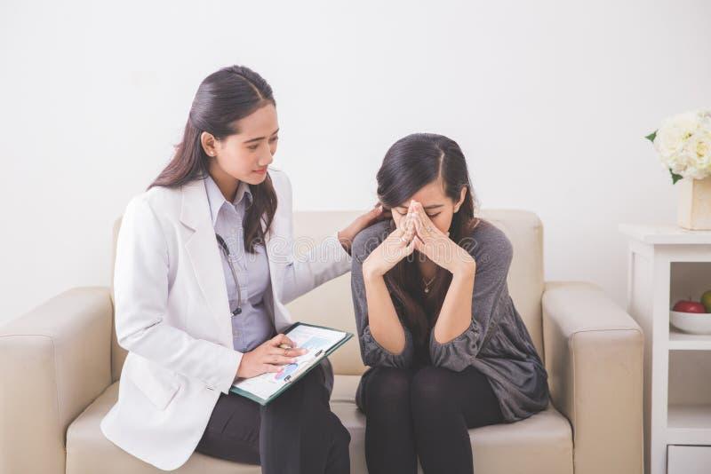 Asiatisk kvinnlig tålmodig gråt, medan konsultera hennes hälsoproblem arkivbilder