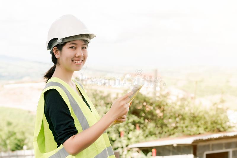 Asiatisk kvinnlig tekniker Put på en vit säkerhetshatt som bär en grön säkerhetsskjortaställning för konstruktionskontroll i kons arkivbild