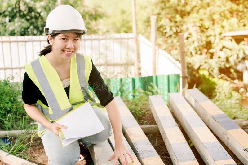 Asiatisk kvinnlig tekniker Wearing en grön säkerhetsskjorta som sitter i konstruktionsområdet royaltyfria bilder
