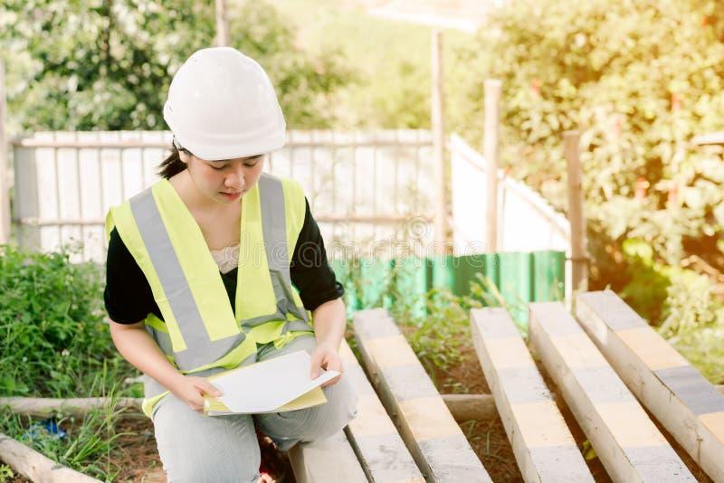 Asiatisk kvinnlig tekniker Wearing en grön säkerhetsskjorta som sitter i konstruktionsområdet arkivfoto