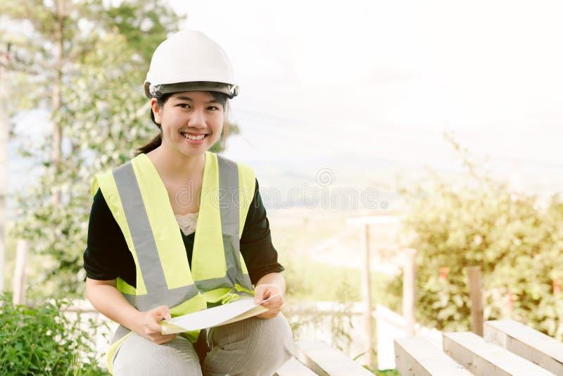 Asiatisk kvinnlig tekniker Wearing en grön säkerhetsskjorta som sitter i konstruktionsområdet arkivbild