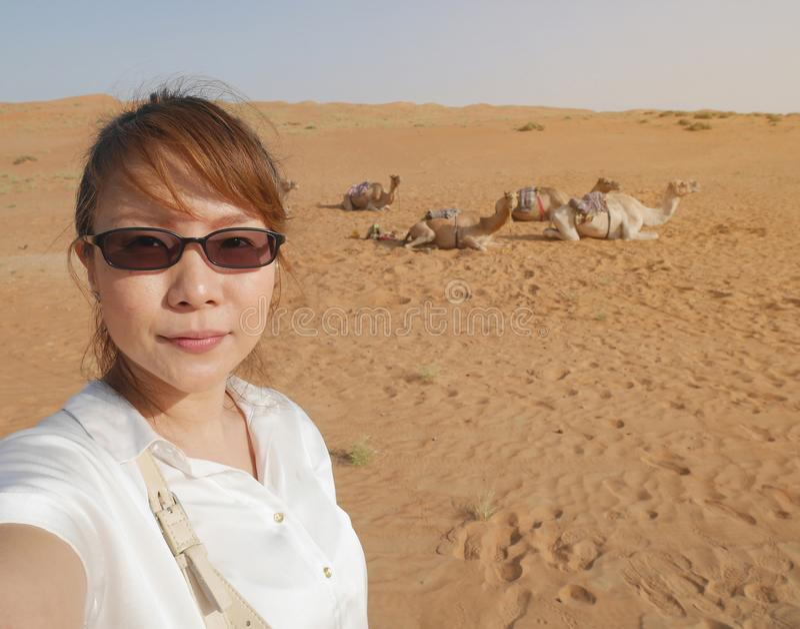 Asiatisk kvinnlig turist som tar selfie på den Wahiba öknen i Oman med arkivbilder