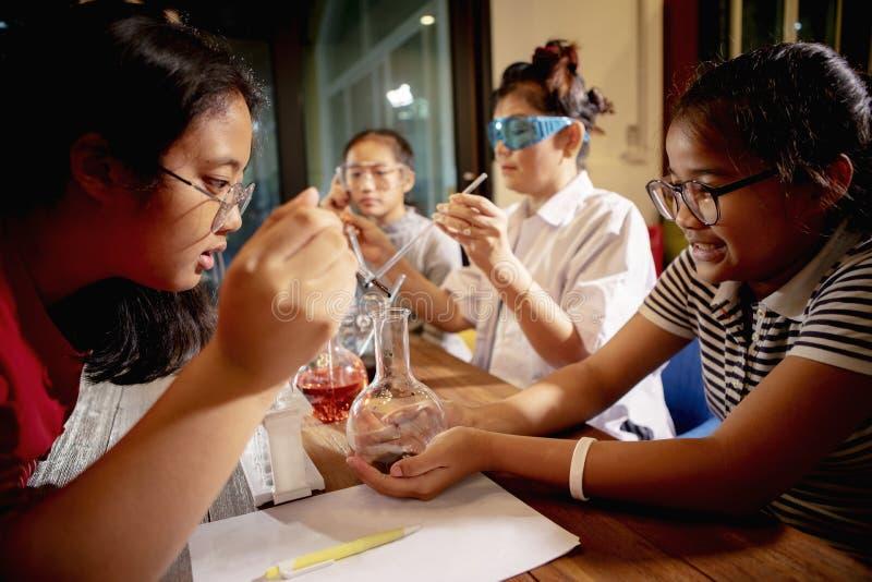 Asiatisk lärare och student i rum för skolavetenskapslaboratorium arkivbild