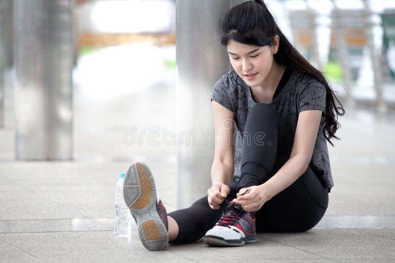 asiatisk löpare för ung kvinna för kondition som binder skosnöre, innan att köra genomköraren som övar med en vattenflaska på gat arkivfoto
