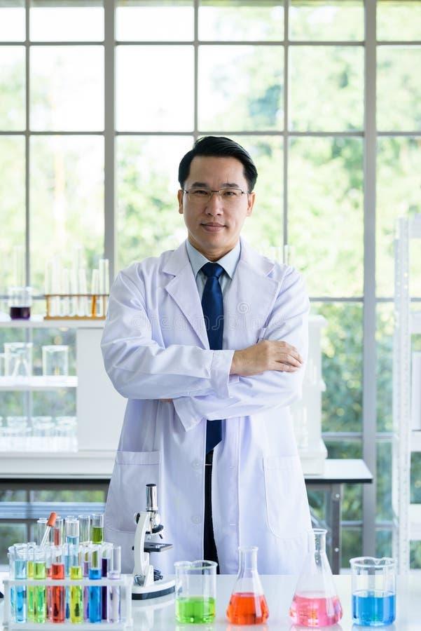 Asiatisk laboratoriumforskareman som arbetar på labbet med provrör arkivfoton