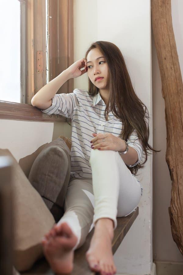 Asiatisk ledsen kvinna som sitter nära det deprimerade fönstret royaltyfria bilder