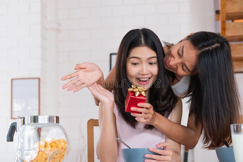 Asiatisk lesbisk paröverraskning, genom att ge gåvan för årsdag av förälskelse på kökfrukosttid hemma LGBTQ-livsstilbegrepp arkivbild
