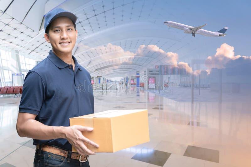 Asiatisk leveransman som rymmer en kartong med bakgrund för internationell flygplats arkivfoto