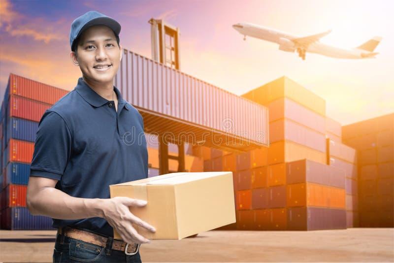 Asiatisk leveransman som rymmer en kartong med logistikgårdbakgrund royaltyfria bilder
