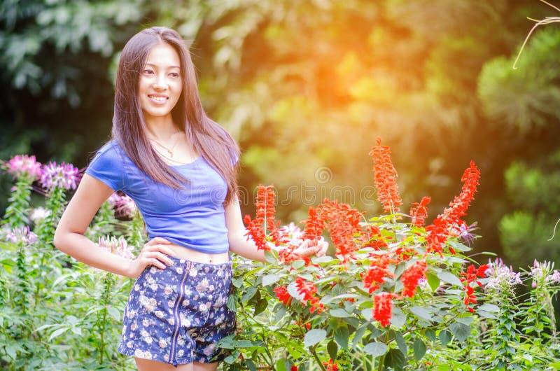 Asiatisk liten flicka för öppna armar i härlig blommavåräng royaltyfri foto