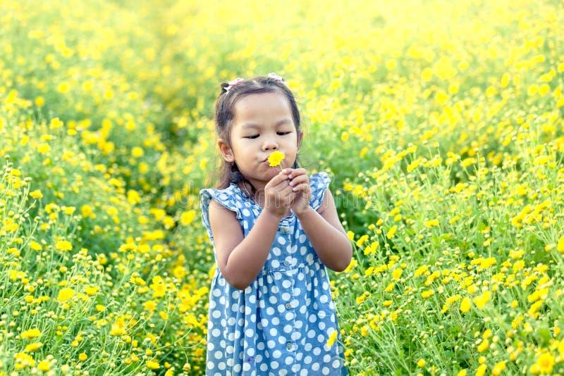 Asiatisk liten flicka för barn som blåser den gula blomman i trädgården arkivbild