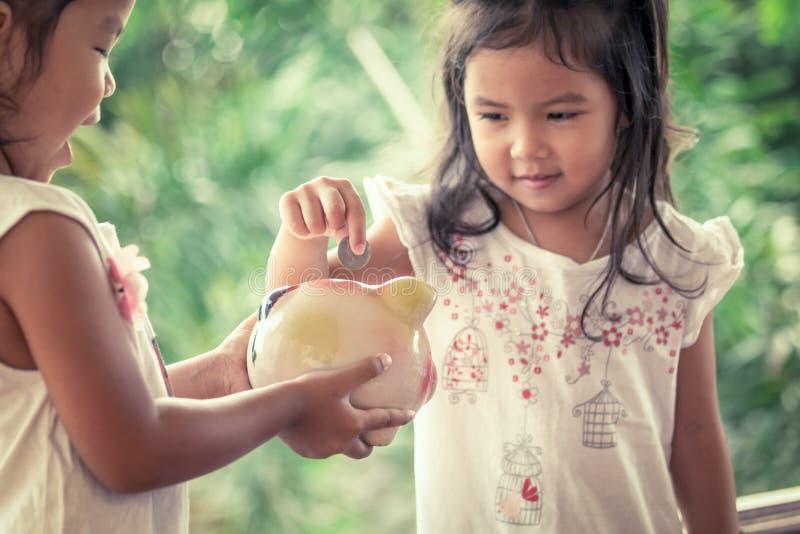 Asiatisk liten flicka för barn som sätter myntet in i spargrisen arkivfoto