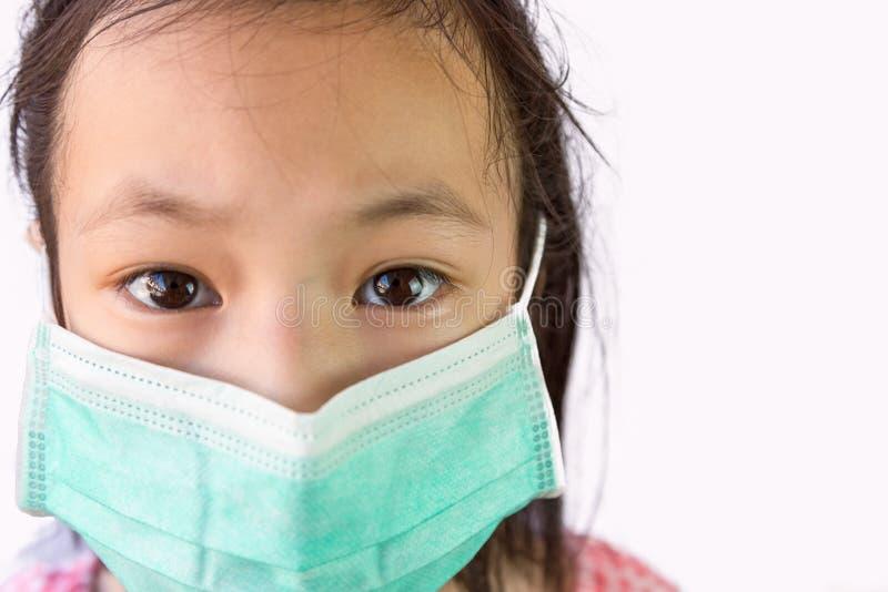 Asiatisk liten flicka för stående i en medicinsk maskering som isoleras på vit bakgrund, barn som bär den hygieniska maskeringen, royaltyfri foto