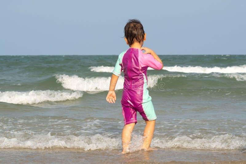Asiatisk liten flicka i baddräkt som går till havet Favorit- ställe av sommarsäsongen royaltyfria foton