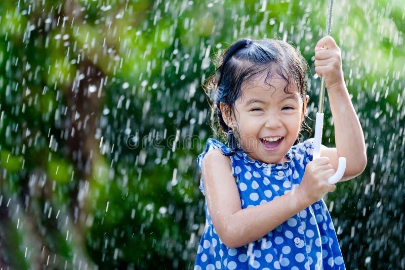 Asiatisk liten flicka med paraplyet i regn royaltyfri fotografi