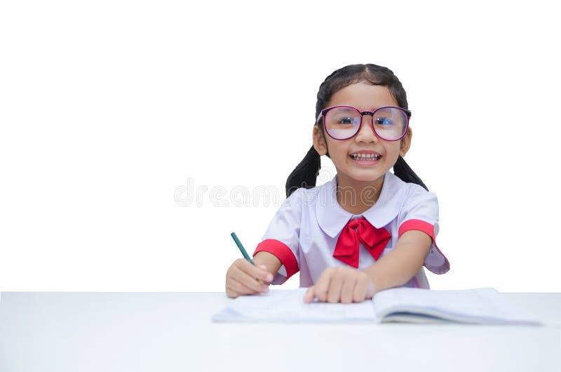 Asiatisk liten flicka som gör läxa med leendet som isoleras på vita lodisar arkivbild