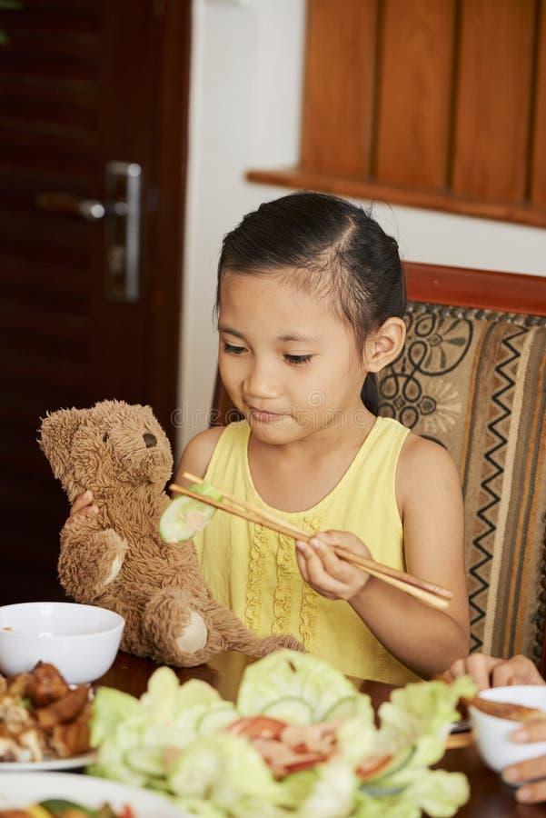 Asiatisk liten flicka som har matställen royaltyfri fotografi