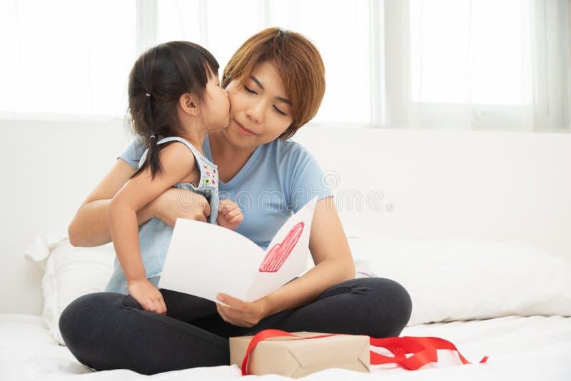 Asiatisk liten flicka som kysser hennes moder royaltyfri bild